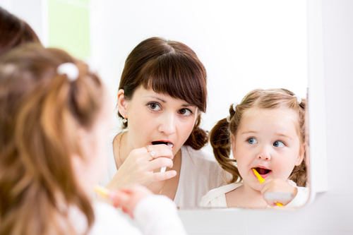 woman and little girl brushing teeth
